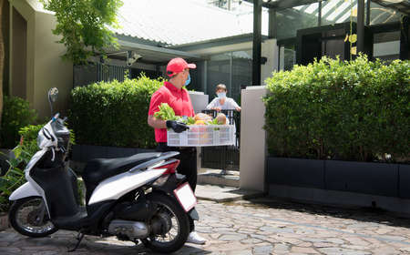 Asian delivery man wearing face mask and gloves in red uniform delivering  groceries box of food, fruit, vegetable and drink to recipient during COVID-19 outbreak