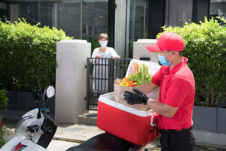 Asian delivery man wearing face mask and gloves in red uniform delivering  groceries bag of food, fruit, vegetable and drink to recipient during COVID-19 outbreak