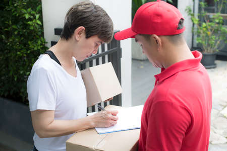 Asian delivery man in red uniform delivering parcel box to woman recipient at home