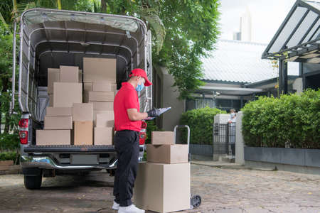 Asian delivery man wearing face mask and gloves in red uniform delivering parcel box to recipient during COVID-19 outbreak