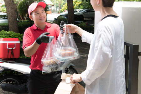 Asian delivery man in red uniform delivering shopping bags of food and drink to woman recipient at home Imagens