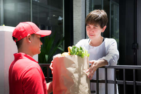 Asian delivery man in red uniform delivering  groceries bag of food, fruit, vegetable and drink to woman recipient at home Imagens