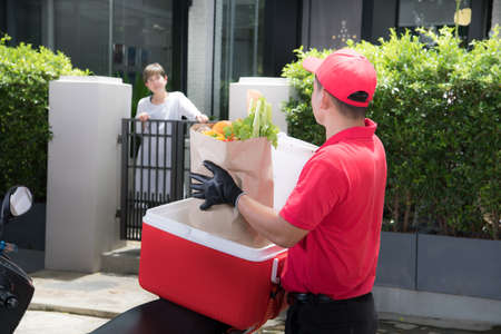 Asian delivery man in red uniform delivering  groceries box of food, fruit, vegetable and drink to woman recipient at home Banque d'images