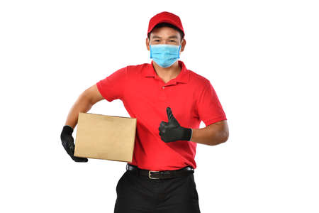 Happy young Asian delivery man in red uniform, medical face mask, protective gloves carry cardboard box in hands isolated on white background. Delivery guy give parcel shipment. Safe delivery Banque d'images