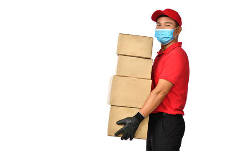 Asian delivery man wearing face mask and gloves in red uniform delivering parcel box isolated on white background during COVID-19 outbreak