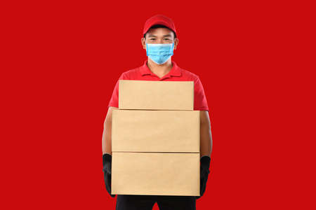 Happy young Asian delivery man in red uniform, medical face mask, protective gloves carry cardboard box in hands on red background. Delivery guy give parcel shipment. During COVID-19 outbreak