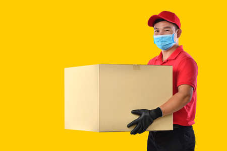Happy young Asian delivery man in red uniform, medical face mask, protective gloves carry cardboard box in hands on yellow background. Delivery guy give parcel shipment. During COVID-19 outbreak
