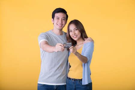 Young Asian couple showing credit card isolated on yellow background