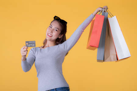 Beautiful young Asian woman with colourful shopping bags and credit card isolated on yellow background Banque d'images - 155898023