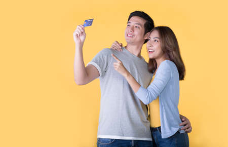Young Asian couple with credit card isolated on yellow background Banque d'images