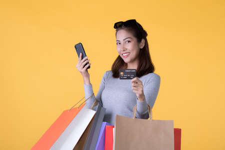 Beautiful young Asian woman with colourful shopping bags with smart phone and credit card isolated on yellow background Banque d'images - 155898025