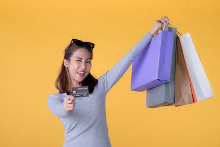 Beautiful young Asian woman with colourful shopping bags and credit card isolated on yellow background Banque d'images - 155898028