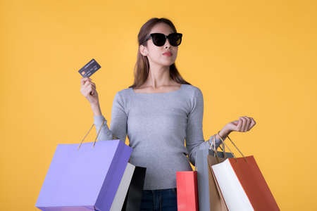 Beautiful young Asian woman with colourful shopping bags and credit card isolated on yellow backgroun