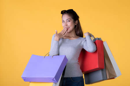 Beautiful young Asian woman carrying shopping bags looking surprised and happy isolated on yellow background Banque d'images - 156241039