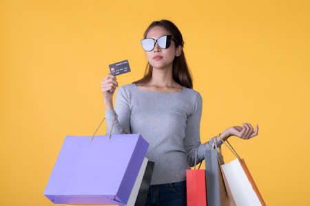 Beautiful young Asian woman with colourful shopping bags and credit card isolated on yellow background