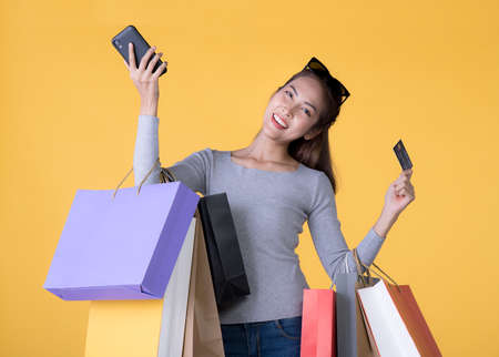 Beautiful young Asian woman with colourful shopping bags with smart phone and credit card isolated on yellow background Banque d'images