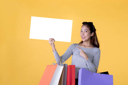Beautiful young Asian woman carrying shopping bags and holging white banner with copy space isolated on yellow background