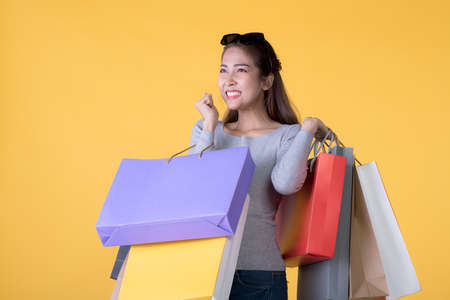 Beautiful young Asian woman carrying shopping bags looking surprised and happy isolated on yellow background Banque d'images - 156241048