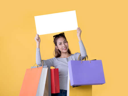 Beautiful young Asian woman carrying shopping bags and holging white banner with copy space isolated on yellow background Banque d'images - 156241049