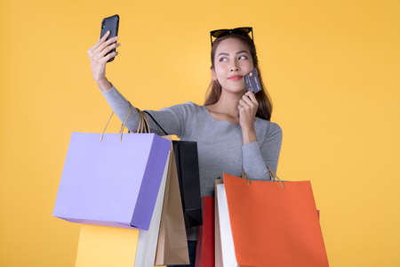 Beautiful young Asian woman with colourful shopping bags with credit card and taking selfie with smartphone isolated on yellow background