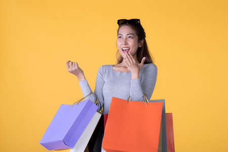 Beautiful young Asian woman carrying shopping bags looking surprised and happy isolated on yellow background Banque d'images - 156241054