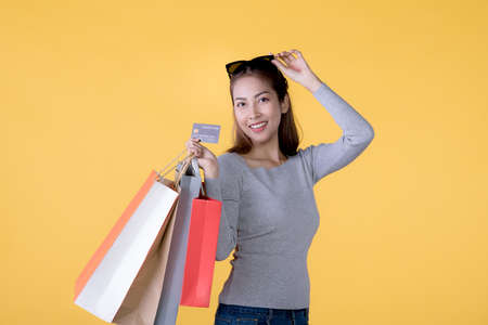 Beautiful young Asian woman with colourful shopping bags and credit card isolated on yellow background Banque d'images - 156241056