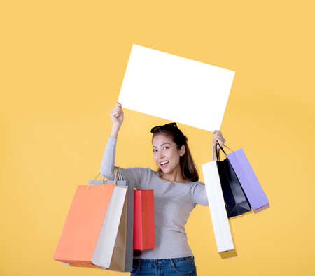 Beautiful young Asian woman carrying shopping bags and holging white banner with copy space isolated on yellow background Banque d'images - 156241057