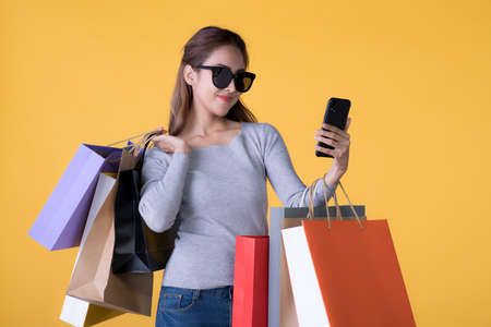 Beautiful young Asian woman with colourful shopping bags and smartphone isolated on yellow backgroun