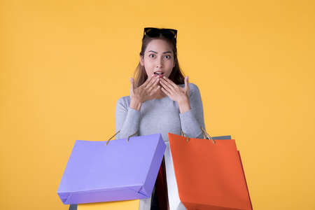 Beautiful young Asian woman carrying shopping bags looking surprised and happy isolated on yellow background
