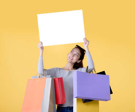 Beautiful young Asian woman carrying shopping bags and holging white banner with copy space isolated on yellow background Banque d'images - 156241090
