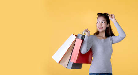 Beautiful young Asian woman carrying shopping bags looking surprised and happy isolated on yellow banner background with copy space Banque d'images