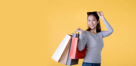 Beautiful young Asian woman carrying shopping bags looking happy isolated on yellow banner background with copy space