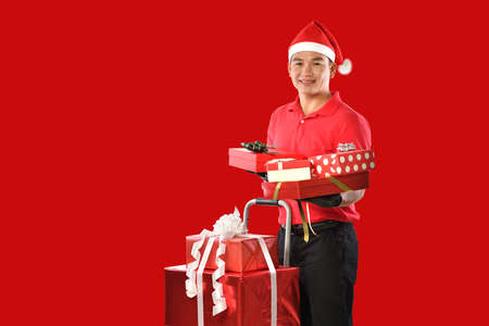 Happy young Asian delivery man in red uniform, christmas hat carry boxes of presents in hands on red background during christmas festivities Banque d'images - 156241094