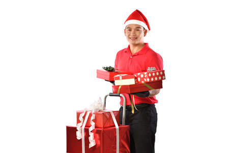 Happy young Asian delivery man in red uniform, Christmas hat carry boxes of presents in hands isolated on white background during Christmas festivities Banque d'images - 156241095