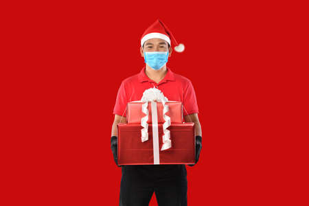 Happy young Asian delivery man in red uniform, medical face mask, protective gloves, christmas hat carry boxes of presents in hands on red background during COVID-19 outbreak and christmas festivities Banque d'images - 156241099