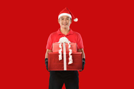 Happy young Asian delivery man in red uniform, christmas hat carry boxes of presents in hands on red background during christmas festivities