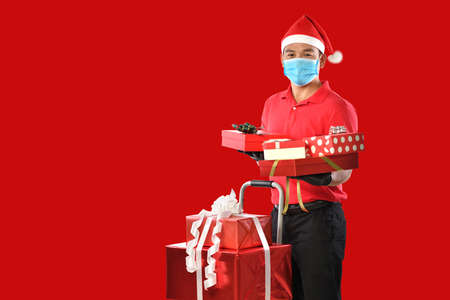 Happy young Asian delivery man in red uniform, medical face mask, protective gloves, christmas hat carry boxes of presents in hands on red background during COVID-19 outbreak and christmas festivities Banque d'images - 156241101