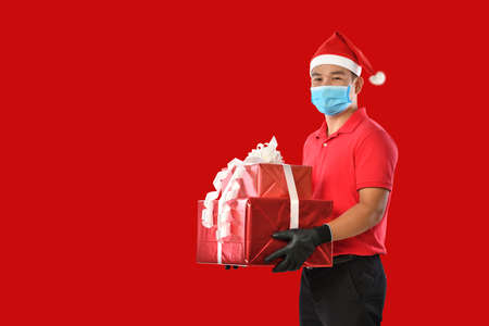 Happy young Asian delivery man in red uniform, medical face mask, protective gloves, christmas hat carry boxes of presents in hands on red background during COVID-19 outbreak and christmas festivities