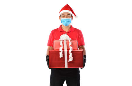 Happy young Asian delivery man in red uniform, medical face mask, protective gloves, christmas hat carry boxes of presents in hands isolated on white background during COVID-19 outbreak and christmas festivities