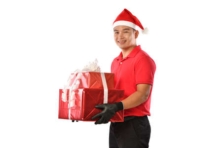 Happy young Asian delivery man in red uniform, Christmas hat carry boxes of presents in hands isolated on white background during Christmas festivities