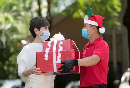 Asian delivery man wearing face mask and gloves in red uniform and Christmas hat delivering present and gift boxes to woman recipient during COVID-19 outbreak for Christmas festival