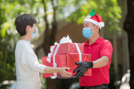 Asian delivery man wearing face mask and gloves in red uniform and Christmas hat delivering present and gift boxes during COVID-19 outbreak for Christmas festival Banque d'images