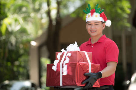 Asian delivery man in red uniform and Christmas hat delivering present and gift boxes to recipient for Christmas festival Banque d'images