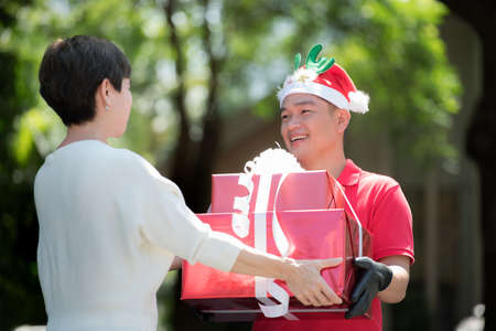 Asian delivery man in red uniform and Christmas hat delivering present and gift boxes to recipient for Christmas festival Banque d'images - 156387762