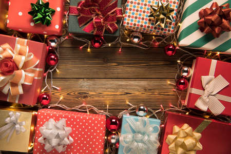 Christmas decoration light and gift boxes on wooden background top view with copy space for frames, presents, and festive Christmas decoration