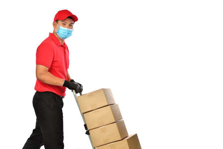 Happy young Asian delivery man in red uniform, medical face mask, protective gloves pushing a hand truck with boxes isolated on white background. Delivery guy give parcel shipment. Safe delivery Banque d'images - 157263501