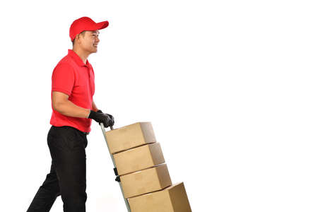 Happy young Asian delivery man in red uniform pushing a hand truck with boxes isolated on white background. Delivery guy give parcel shipment. Banque d'images