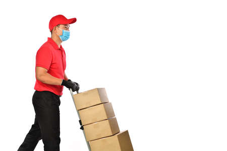 Happy young Asian delivery man in red uniform, medical face mask, protective gloves pushing a hand truck with boxes isolated on white background. Delivery guy give parcel shipment. Safe delivery