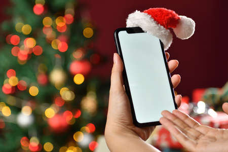 Hand holding the black smartphone with a blank screen and Santa Claus' hat on top on Christmas background Banque d'images - 157272426