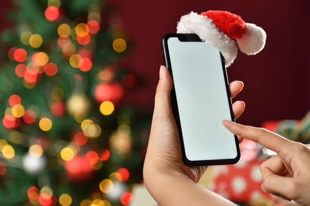 Hand holding the black smartphone with a blank screen and Santa Claus' hat on top on Christmas background